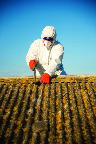 A workman wearing protective clothing and facemask removing asbestos roof tiles from a public shelter, Aberaeron, Wales UK