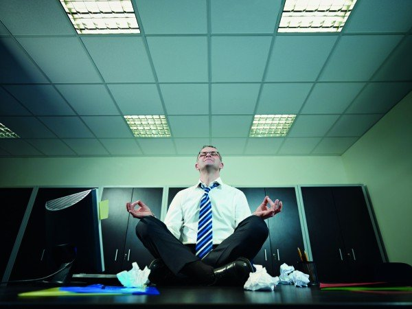 Mature businessman sitting on desk in lotus position. Horizontal shape, full length, Copy space