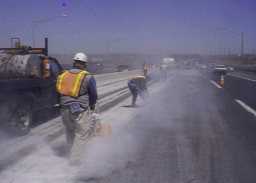 Highway road workers use high power saws