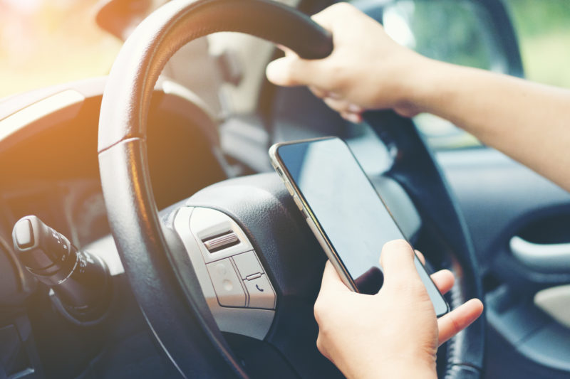 Driving while holding a mobile phone to work ,businessman ,vintage color tone