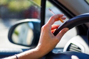 Woman smoking a cigarette at the wheel of a car