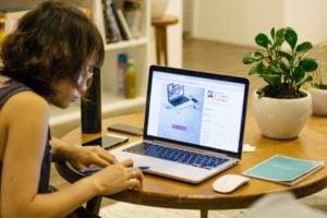 Woman sat at laptop at home